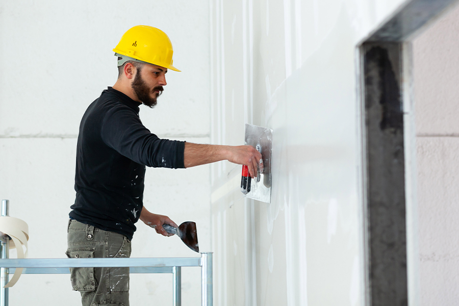 Drywall Contractor Insurance - Drywall Worker in Yellow Helmet Plastering Wall While Standing on Scaffold