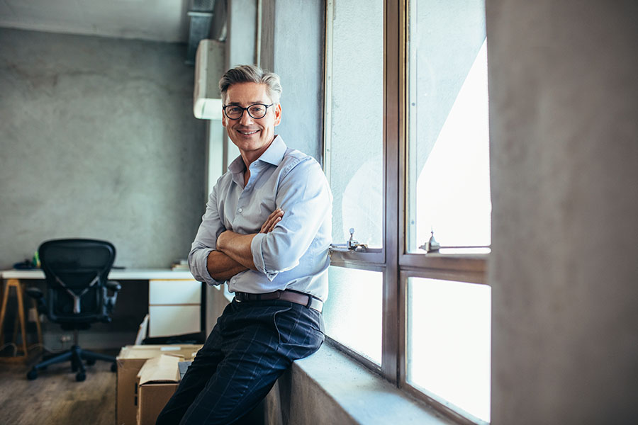 Business Insurance - Portrait of a Mature Smiling Businessman Sitting Next to a Window in the Office
