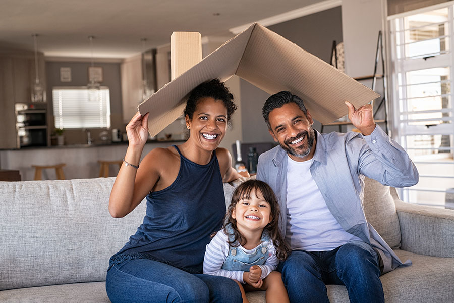 Personal Insurance - Closeup Portrait of a Cheerful Family Sitting on the Sofa Holding up a Piece of Cardboard to Symbolize the Roof of a Home