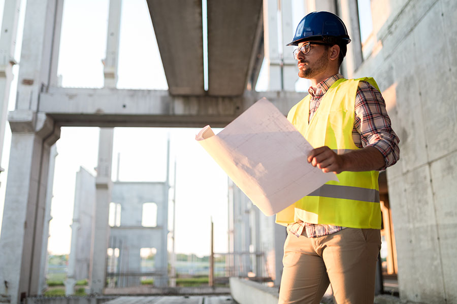Specialized Business Insurance - Closeup Portrait of a Contractor Standing on a Construction Jobsite While Holding Building Blueprints in His Hand