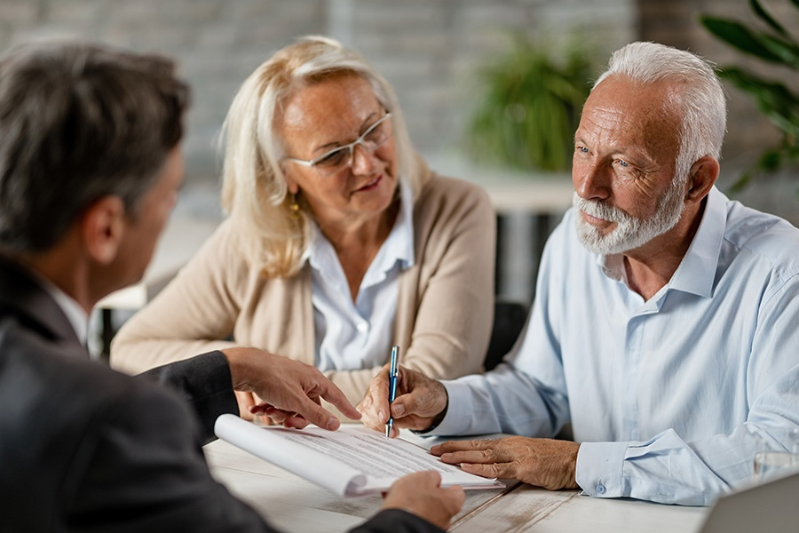 General-Medicare-Couple-Signing-a-Contract-While-Having-a-Meeting-with-an-Insurance-Agent-in-the-Office